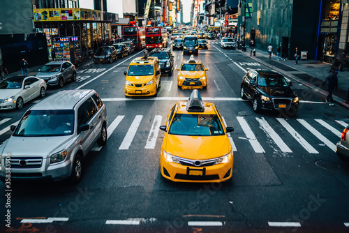 Fototapeta Yellow cabs moving on road of Manhattan passing buildings and commercial on street during daytime, busy traffic on avenues in New York downtown with cars and cab taxis stopping near crossroad in city obraz