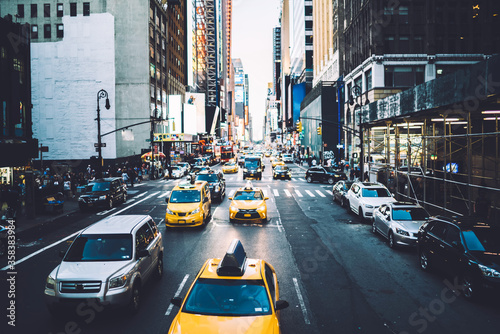 Fototapety, obrazy: Busy avenue street in midtown with high buildings and advertising on fronts and cars driving on road, yellow taxi cabs and automobiles moving on street in New York during daytime with rush traffic