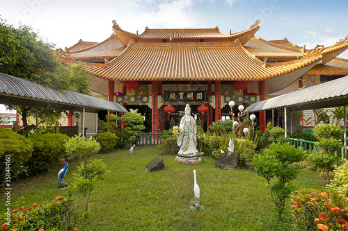 Statuary decorates a lush garden in front of the tile-roofed Toh Tze (Poh Toh Ts Canvas-taulu
