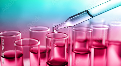 Dropping sample into test tube with liquid on color background, banner design. Laboratory analysis