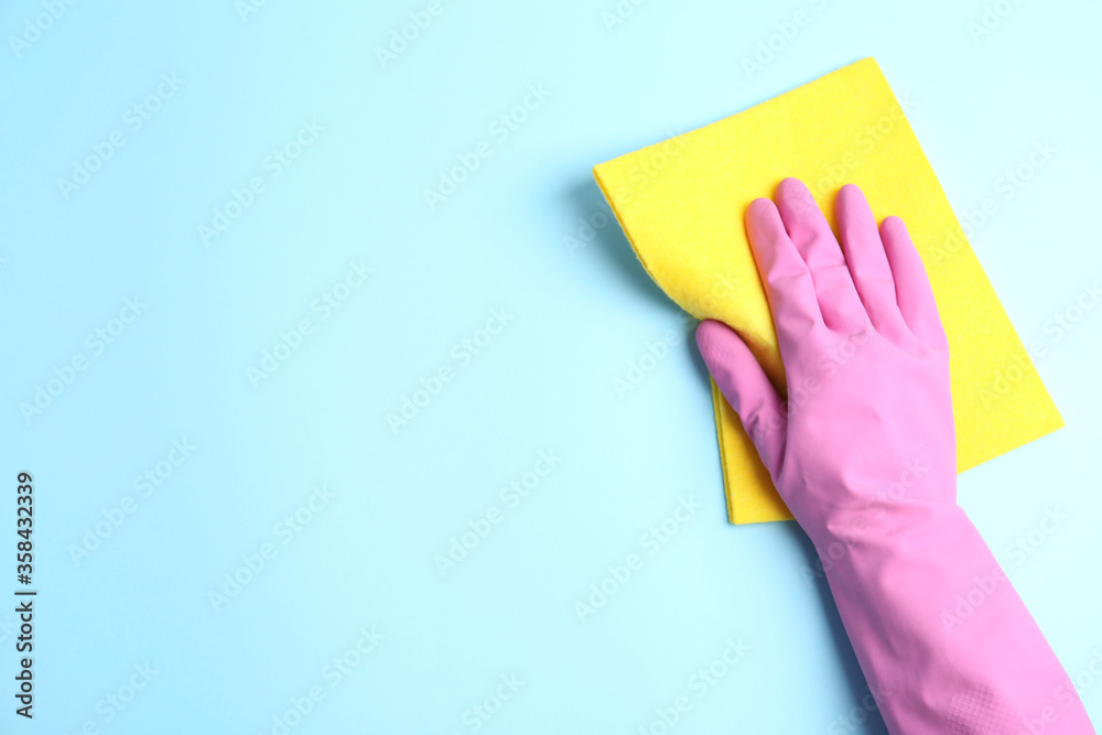 Fototapeta Person in rubber glove with rag on light blue background, closeup of hand. Space for text