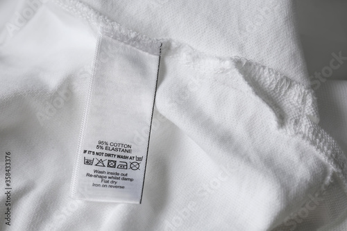 Fotomural Clothing label with care symbols and material content on white shirt, closeup vi