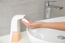 Woman Using Automatic Soap Dis...