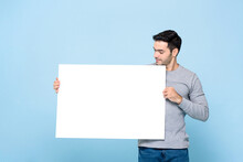Portrait Of Handsome Caucasian Man Holding And Looking At White Placard In Isolated Studio Blue Background