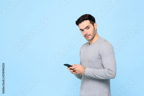 Fotomural Portrait of handsome Caucasian man texting message on mobile phone and looking a