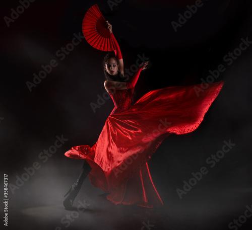 Slika na platnu Flamenco woman spanish dancer in red dres performs with fan in dance at black ba