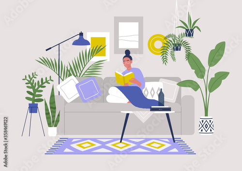 Obraz na plátne Young female character sitting on sofa and reading a book, cozy boho interior wi