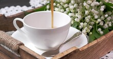 Coffee Is Poured Into A Cup. In The Background A Bouquet Of Flowers
