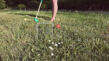 Woman Striking A Bright Turquoise Ball Through A Hoop With A Wooden Mallet While Playing Garden Croquet In Super Slow Motion.
