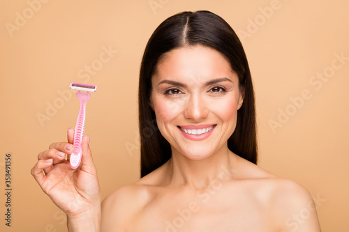 Closeup photo of mature latin naked lady in bathroom holding new shaver model recommending good quality product advert isolated beige pastel color background