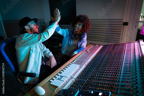 Fototapeta A professional male producer and young african female singer are happy with resu