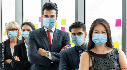 Fototapety, obrazy: Confident business people with face mask protect from Coronavirus or COVID-19.