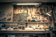 Complete Workbench With A Wall Of Tools In A Workshop. Vintage Look.