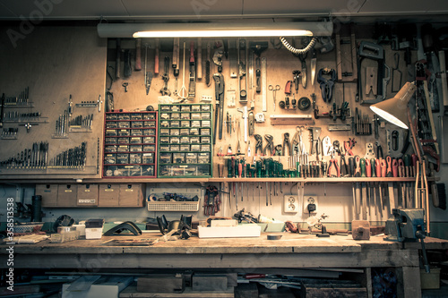 Obraz Complete workbench with a wall of tools in a workshop. Vintage look. - fototapety do salonu