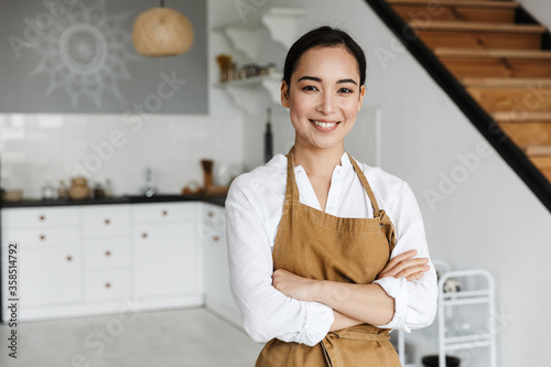 Fotografía Smiling attractive young asian woman wearing apron