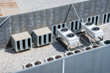 Equipment Of Industrial Air Conditioner Units Surrounded By A Quiet Fence On A Rooftop. HVAC Fan Machines.