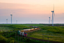 Wind Farm And Moving Train At Sunset