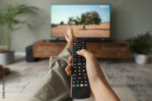 Obraz Woman watching TV at home and holding the remote control - fototapety do salonu
