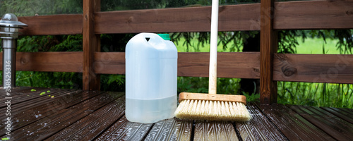 Fototapeta Brush and plastic canister with detergent on a wooden board, wooden terrace