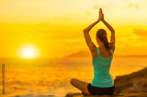 Health and Fitness - Young healthy fit caucasian woman meditating and practicing yoga sitting at the beach and watching the beautiful ocean sunset.