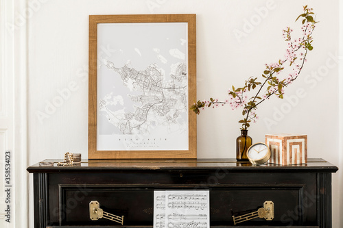 Stylish composition at living room interior with black piano, mock up poster map, dried flowers in vase, decoration and elegant presonal accessories in modern home decor.