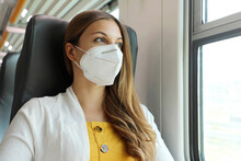 Travel Safely On Public Transport. Young Woman With KN95 FFP2 Face Mask Looking Through Train Window. Train Passenger With Protective Mask Travels Sitting In Business Class Looking Through The Window.