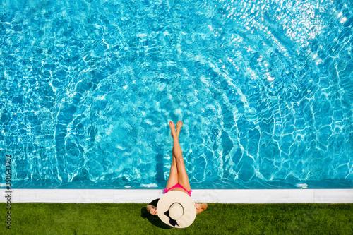 Photo Top Ansicht einer Frau mit Hut die am Rande eines Swimming Pools sitzt und das b