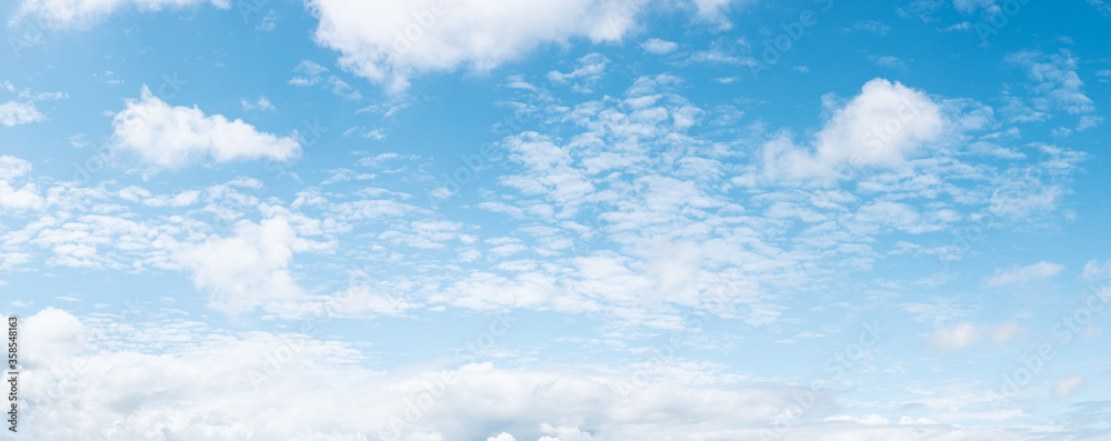 Fototapeta Panoramic blue sky background with small white fluffy clouds, high resolution panorama