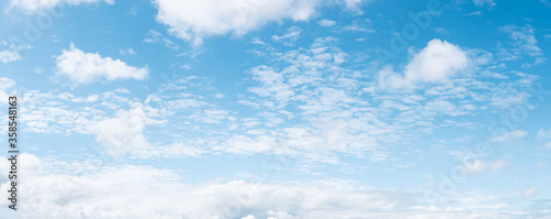 Fotografiet Panoramic blue sky background with small white fluffy clouds, high resolution pa
