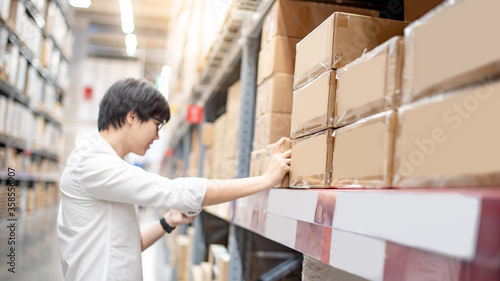 Leinwand Poster Young Asian shopper man picking cardboard box package from product shelf in warehouse
