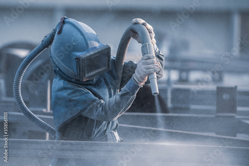 Obraz na plátne Sand blasting process, Industial worker using sand blasting process preparation cleaning surface on steel before painting in factory workshop