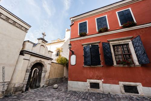 red old house with shutters on windows near arch with door in lviv, ukraine