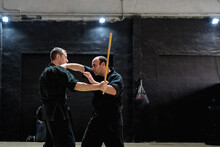Side View Of Strong Adult Male Fighters Practicing Kajukenbo Fight Techniques With Stick During Training In Modern Martial Arts Center