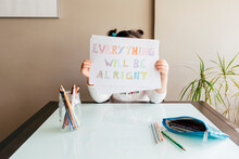Anonymous Girl Sitting At Wooden Table With Colored Pencils And Demonstrating Drawing Saying Everything Will Be Alright At Camera