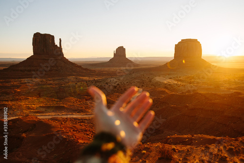 Crop anonymous traveler stretching hand towards sun while admiring amazing landscape of cliffs in desert in California during colorful sunset