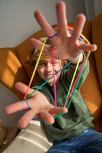 From Above Cheerful Preteen Boy In Casual Clothes Sitting In Cozy Armchair And Playing Interesting Cats Cradle Game While Resting At Home Looking At Camera