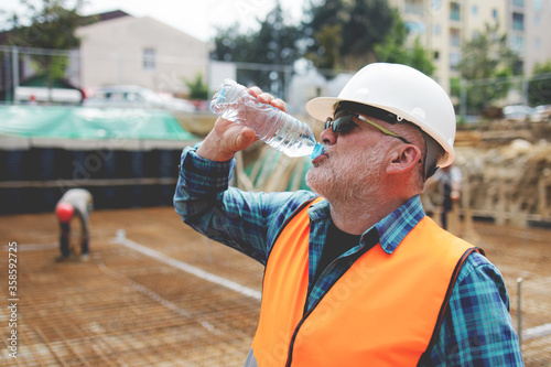 Obraz na plátně Portrait of a worker, an engineer resting and drinking water after hard work on