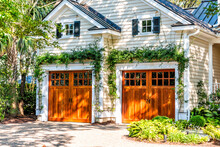 American Residential House Building In Charleston, South Carolina With Two Garage Doors Exterior With Wooden Architecture And Ivy Climbing Plant