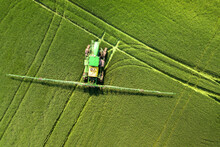 Tractor Spraying Chemical Pesticides With Sprayer On The Large Green Agricultural Field At Spring.