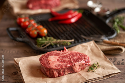 Juicy, seasoned raw ribeye steak on food paper, next to a grill pan, tomatoes on a branch, a head of garlic, red chili peppers, and herbs Fototapet
