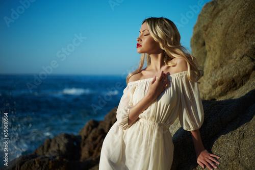 Fototapeta Beautiful blonde woman on the beach. Lady in white dress