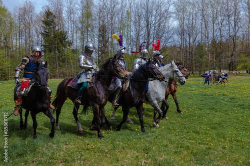 Cuadros en Lienzo A knight in vintage armor of the 15th century rides a horse across a field for a