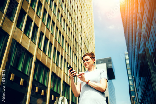 A woman looks at her phone on the street of the city, remote work concept