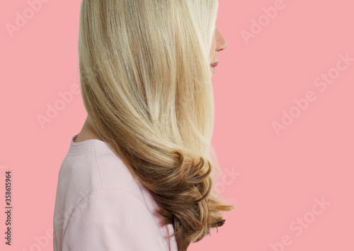 Senior woman with long blonde hair standing over pink background Poster Mural XXL