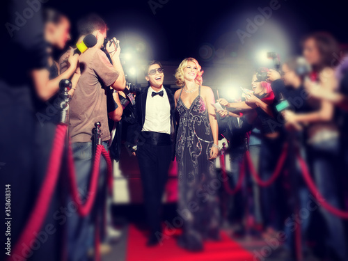 Photographie Celebrity couple arriving a premiere with paparazzi cameras and flashes