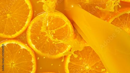 Obraz Freeze motion of pouring orange juice. Top view, close-up. - fototapety do salonu