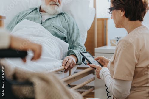 Helpful nurse switching on a professional bed in a nursing home #358627351