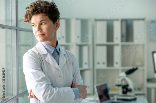Fotografiet Pensive middle-aged female researcher in lab coat standing with crossed arms and
