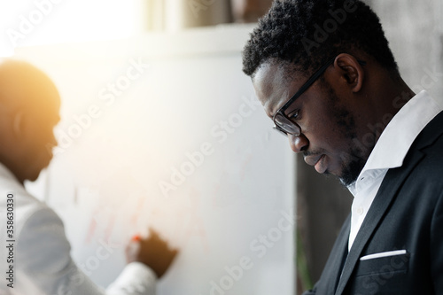 Fototapeta Flogging in profile an african american businessman with glasses and a dark suit looking down