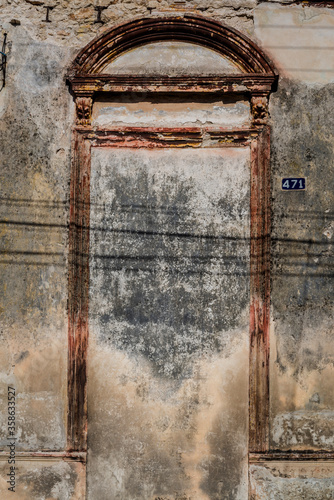 Photo Run down, abandoned, blocked door of which only an architrave and pediment are l